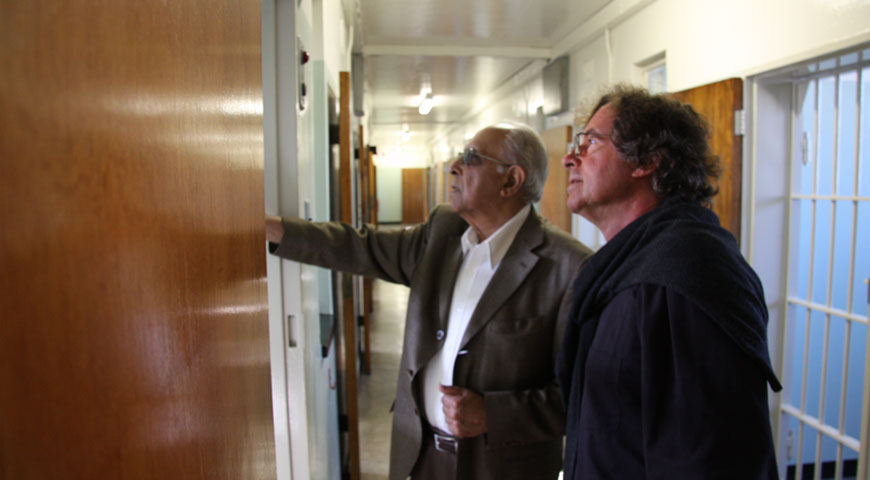 Ahmed Kathrada showing director Michael Wilson his former cell